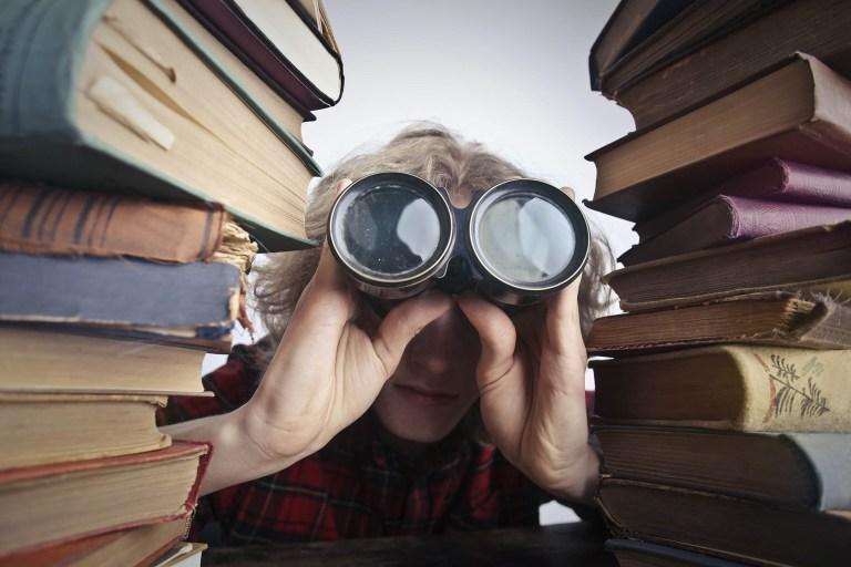 Image d'une personne avec des jumelles devant les yeux entre 2 piles de livres pour illustret la page découvrir Tupin et Semons sur le site de la mairie de Tupin et Semons www.tupinetsemons.fr