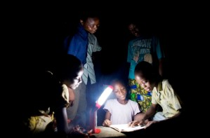 Varios niños vecinos se reúnen para hacer sus tareas con la lámpara LED. Los maestros y personal de la escuela colaboran para el montaje y buen uso de los aparatos. Foto Empowered Playgrounds Inc. (EPI),