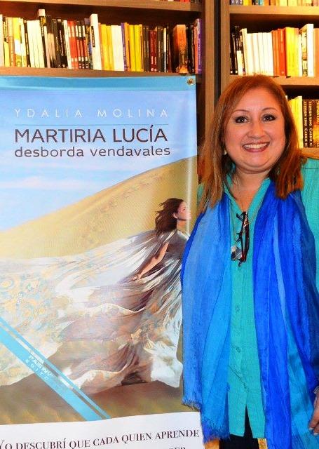 Ydalia junto al afiche de su novela Martiria Lucía desborda vendavales