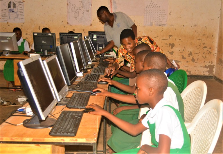 Teacher helps pupils learning to use their new computers at Kalambwer Primary School