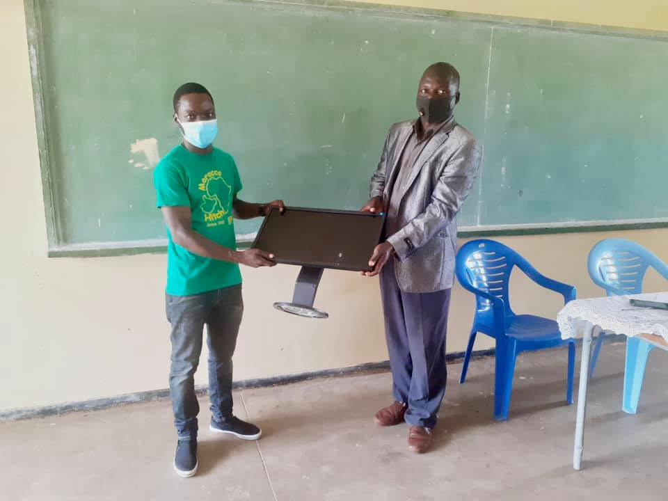 Handing over a monitor to a teacher in Malawi as the CYD team set up a computer lab.