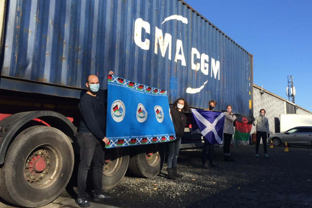 Shipping volunteers with flags in front of container