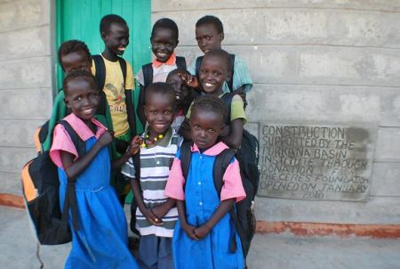 Students at Telesgaye Primary School standing in front of teachers' quarters funded by Ceres