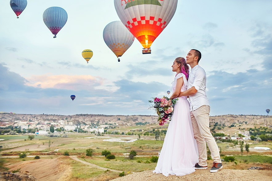 Man and woman hugging standing background of balloons in Cappadocia, Turkey.