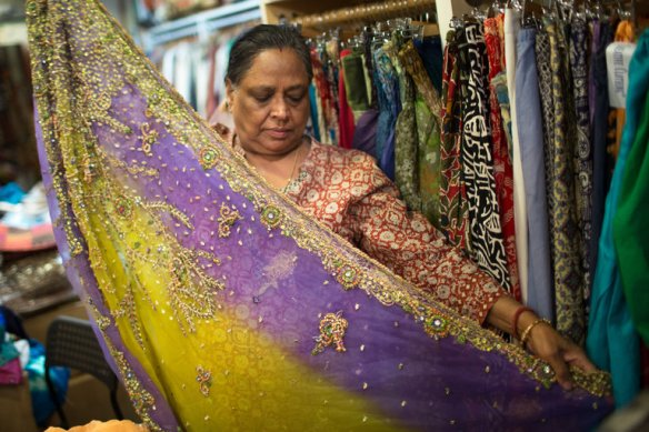 Saroj Goyal organized fabrics at Dress Shoppe II, an Indian textiles store in the East Village. Credit Santiago Mejia/The New York Times