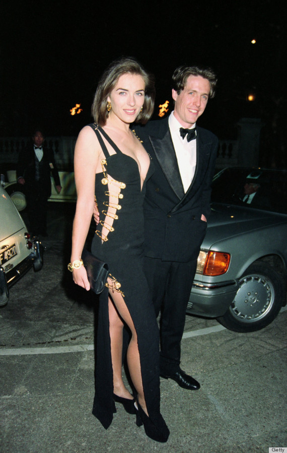 Elizabeth Hurley (with Hugh Grant) in her famous safety-pin dress by Versace - Photo credit: Getty Images