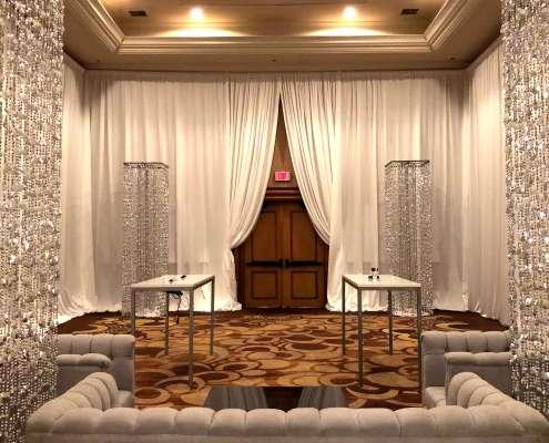 Beaded Silver Columns inside a white velour / white velvet draped room From Turn of Events Las Vegas Rental Drapery