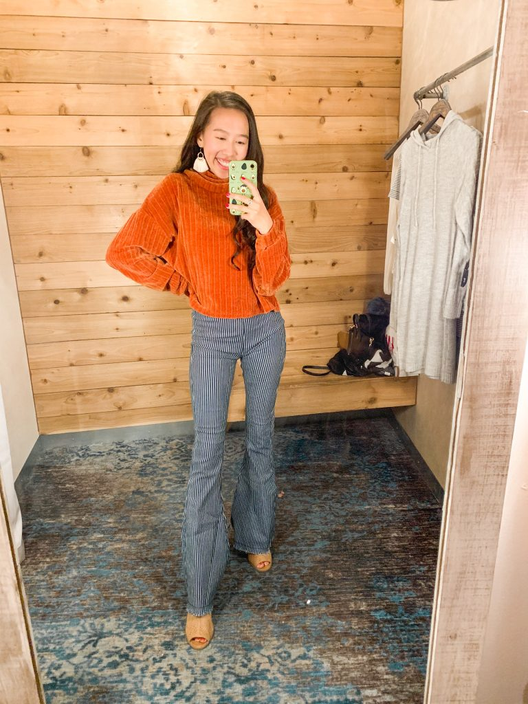 woman taking mirror selfie in sweater and flare jeans