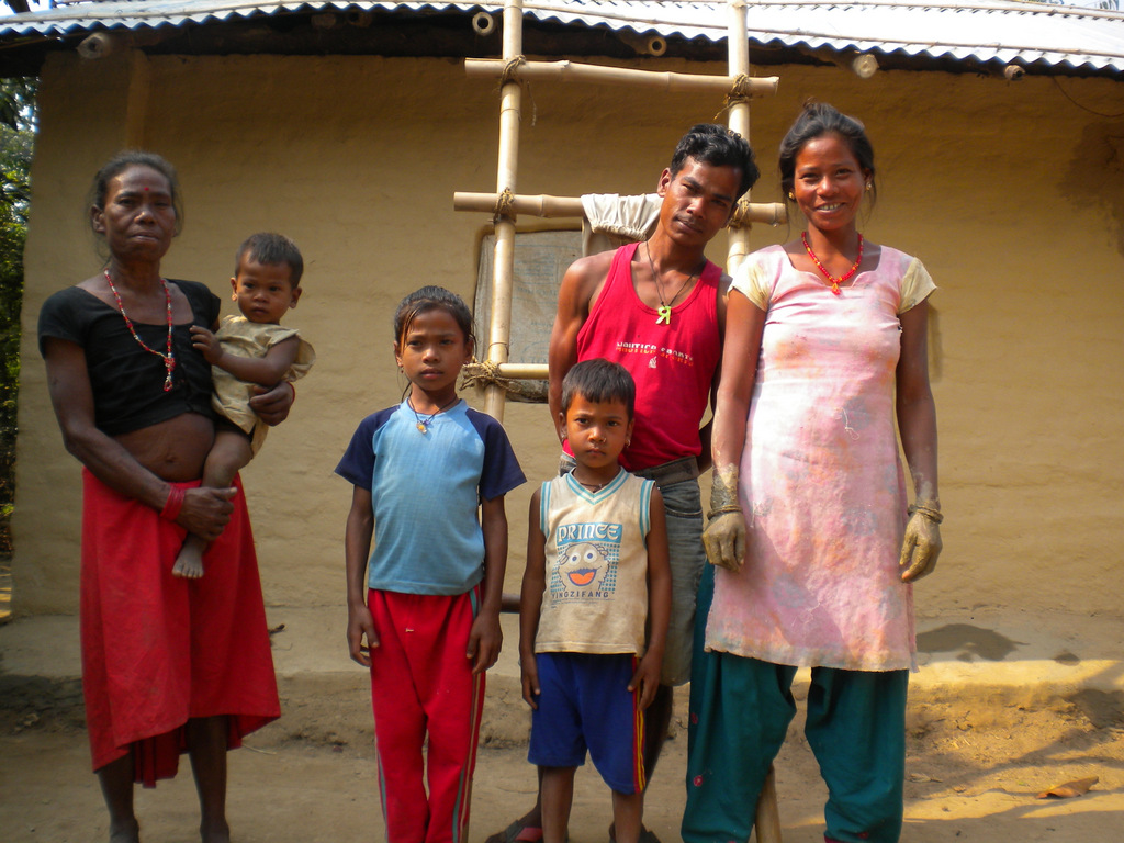 Raja Ram Tharu and his family stand proud in front of their newly-renovated roof