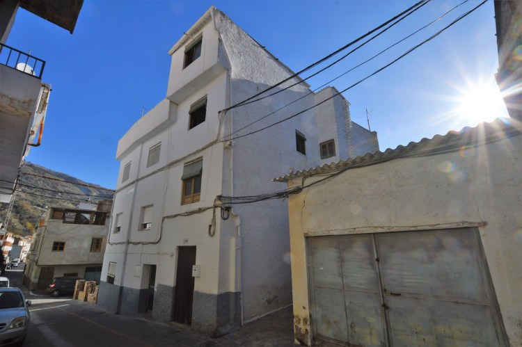 A photo of a tall, white townhouse, typical of the Alpujarras