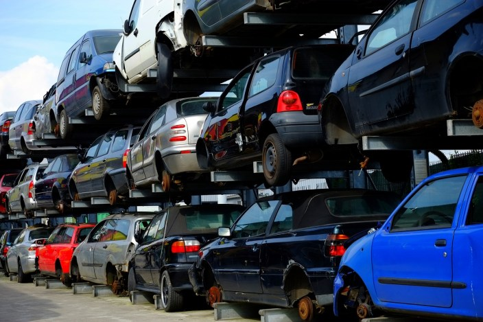 Photo of cars piled up without tyres at a scrapyard