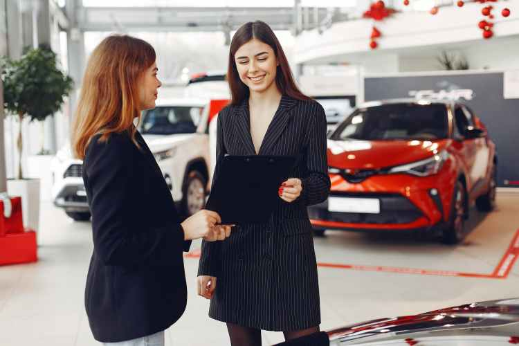 positive gorgeous agent sharing contract with client in car salon