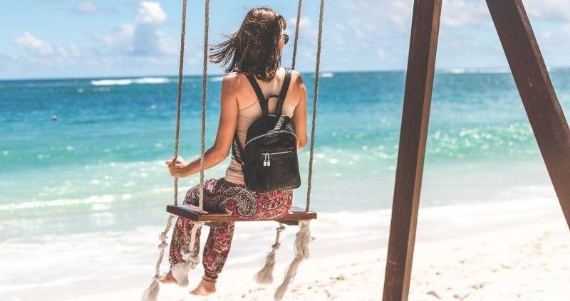 Bolsos y Mochilas de Mujer con USB | Chica con un columpio en la playa