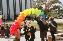 """Shortly after 12 p.m., the event's host played Diana Ross's """"I'm Coming Out"""" and invited all members of the LGBTQ community to walk through the arch to show off their pride."""