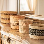 Four handmade baskets on top of a chimney in front of a mirror