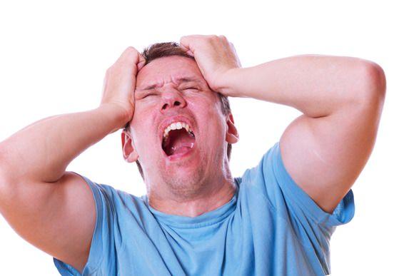 痛みに悶え苦しむ男性の画像