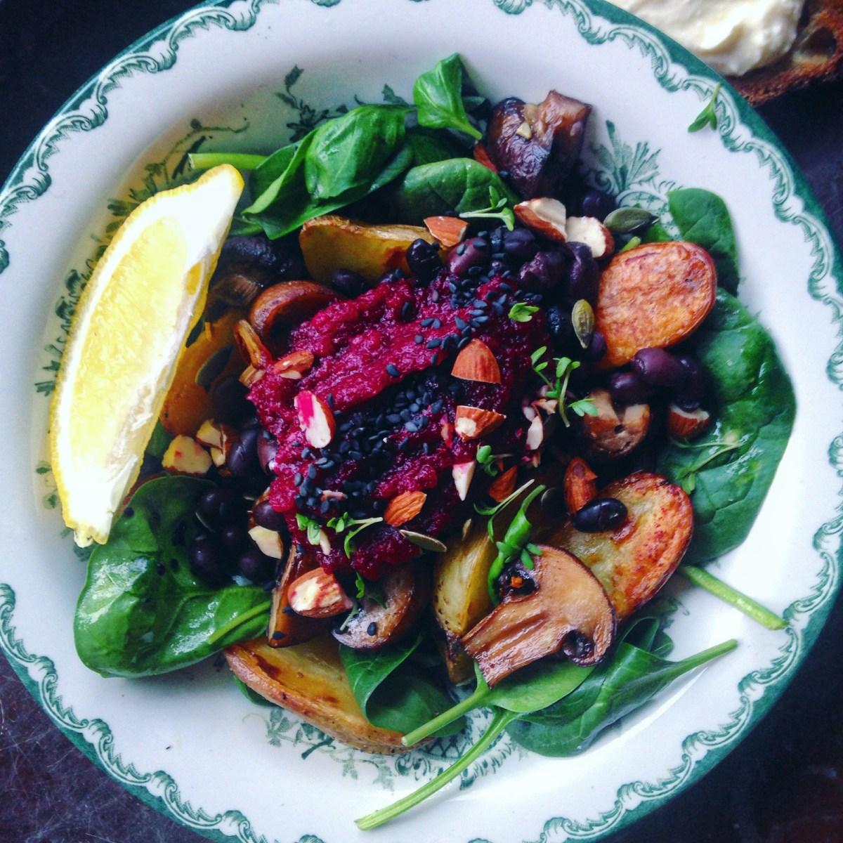 Matig vegansk sallad med rostad potatis, vitlöksstekt svamp, rödbeta, mandel, svarta bönor och citrondressad spenatsallad
