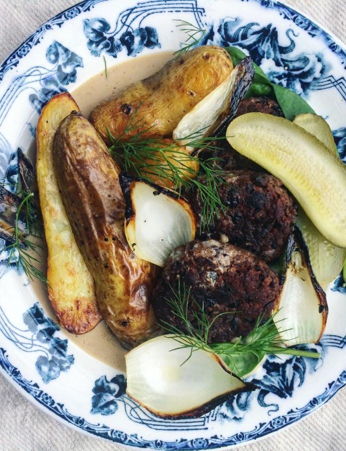 Vegansk pannbiff med gräddsås, rostad potatis, saltgurka, dill och sotad lök