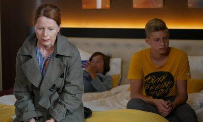 aktorka Ewa Skibińska siedzi smutna na łóżku w hotelu, w tle serialowe wnuki.