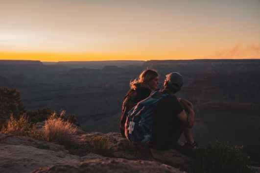 Prvi spoj u prirodi. Muškarac s velikim ruksakom sjedi pored žene na rubu litice u sumrak.