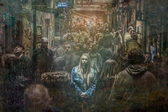 Sramežljiva i povučena žena u traper jakni hoda u gomili ljudi na užurbanoj gradskoj ulici
