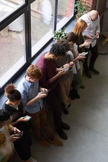 Ljudi stoje jedno pored drugog i gledaju svaki u svoj mobitel. Tako ostavljaju vrlo loš prvi dojam.