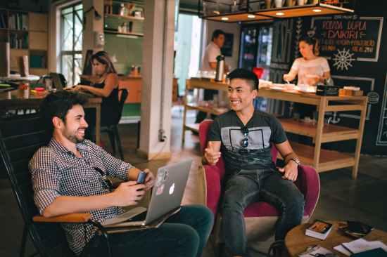 Dvojica nasmijanih muškaraca sjede u kafiću i razgovaraju. Ostavljaju dobar dojam jedno drugome.