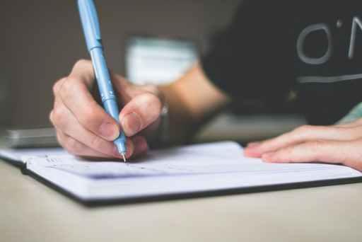 Muškarac u crnoj majici plavom olovkom piše u bilježnicu s kojim prijateljima treba prekinuti prijateljstvo.