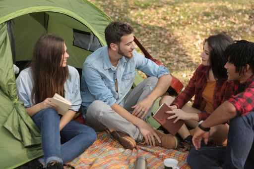 Dva muškaraca i dvije žene sjede ispred šatora i razgovaraju koristeći svoje socijalne vještine. Odlična prigoda za upoznati nove prijatelje.