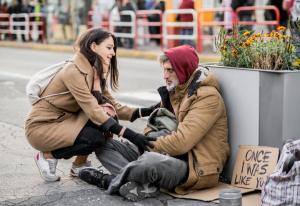 woman kneeling to help homeless man