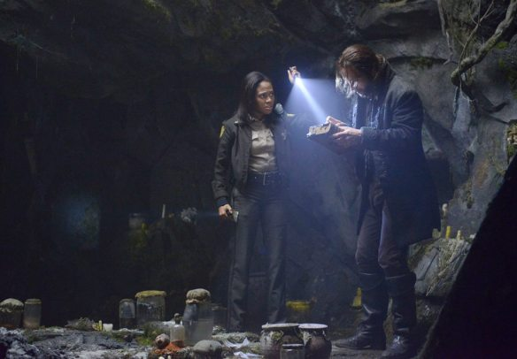 Ichabod and Abbie examine George Washington's bible in a cave