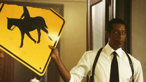 Frank Irving frowns as he holds a roadsign altered to depict the headless horseman on Sleepy Hollow