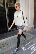 Cara delevingne look cool by pairing denim shorts with knee high socks and sneakers