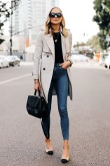 Woman wearing trench coat black sweater denim skinny jeans chanel slingbacks polene number one handbag monochrome black