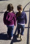 Händehaltende, auf einer Strasse gehende Zwillinge