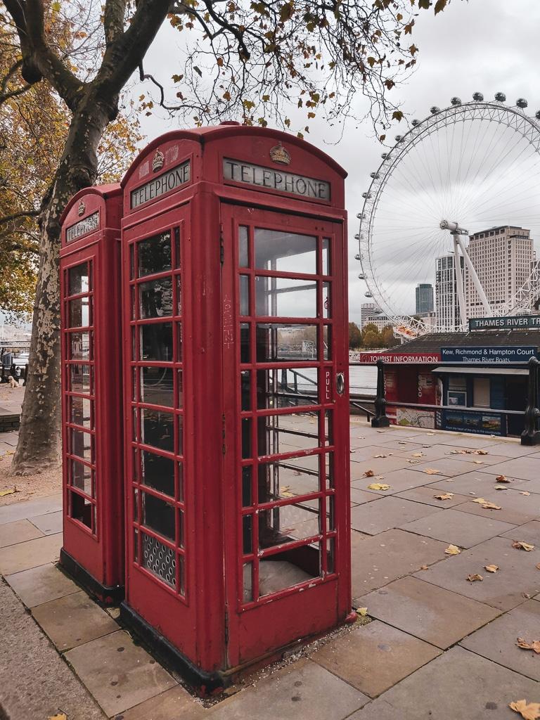 une photo avec des cabines téléphoniques anglaises rouges et le grande roue London Eye