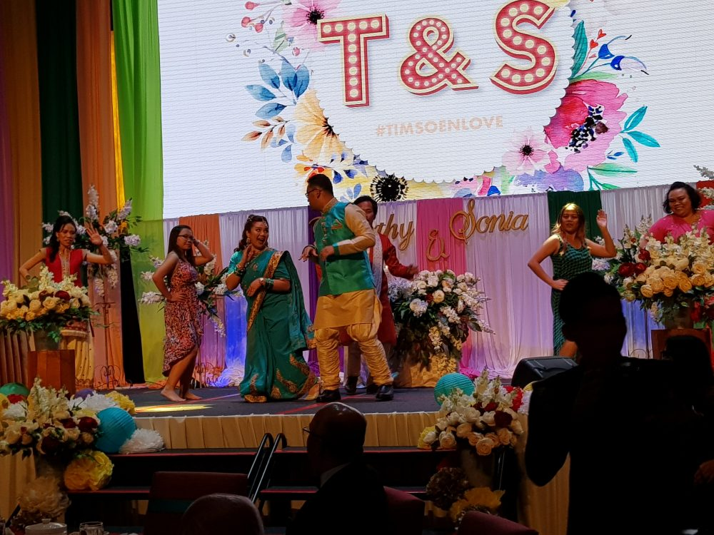 Timothy and Sonia (in green outfits) dancing on stage to Indian music