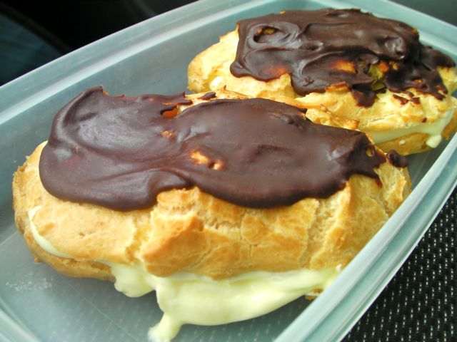 Container holding two chocolate glazed cream eclairs