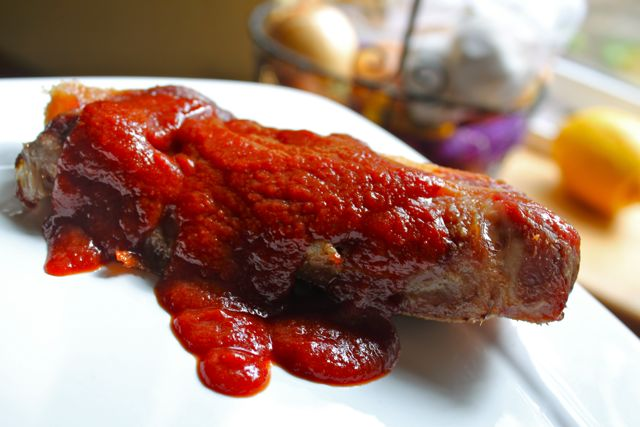 White plate with a single country-style rib covered in soppin'sauce