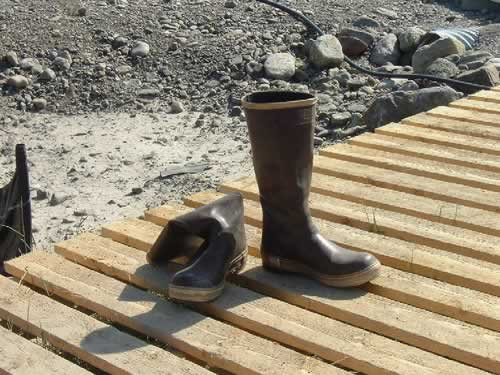 A pair of black and yellow fisherman's boots sitting on a dock