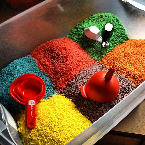 large plastic bin full of six piles of colored rice: blue, red, green, yellow, purple and orange