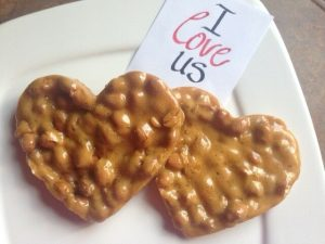 """Two heart-shaped peanut brittle """"cookies"""" on a white plate with a note that reads, """"I love us."""""""