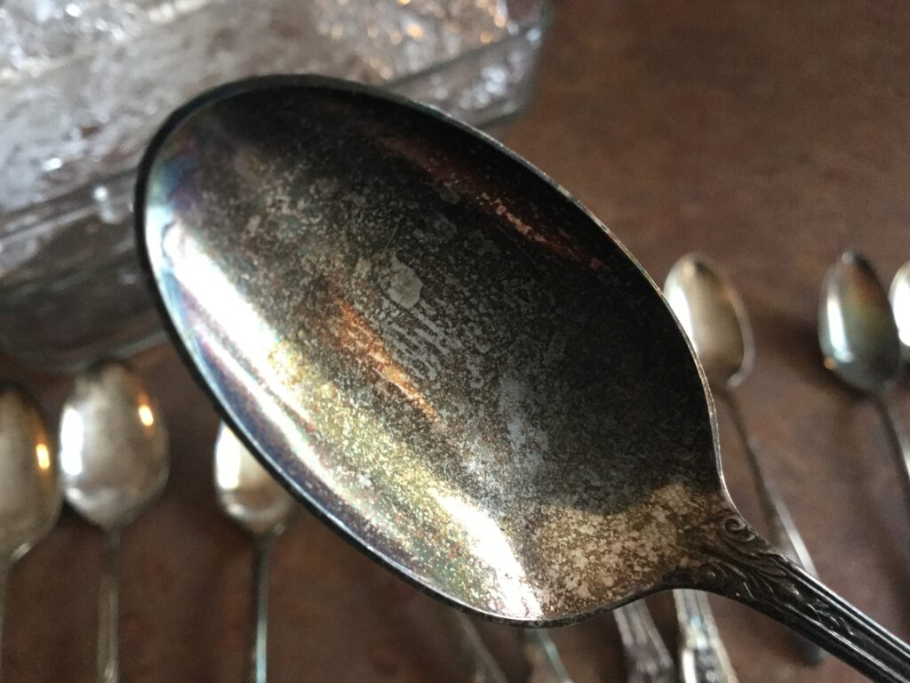 A spoon in the foreground showing tarnish