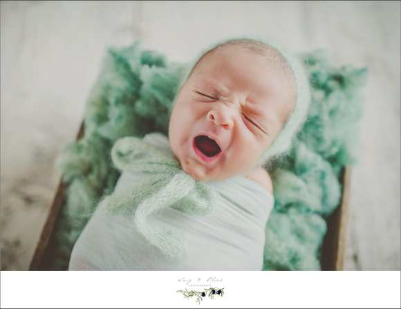 unhappy baby, swaddled, green quilt, green swaddle, baskets