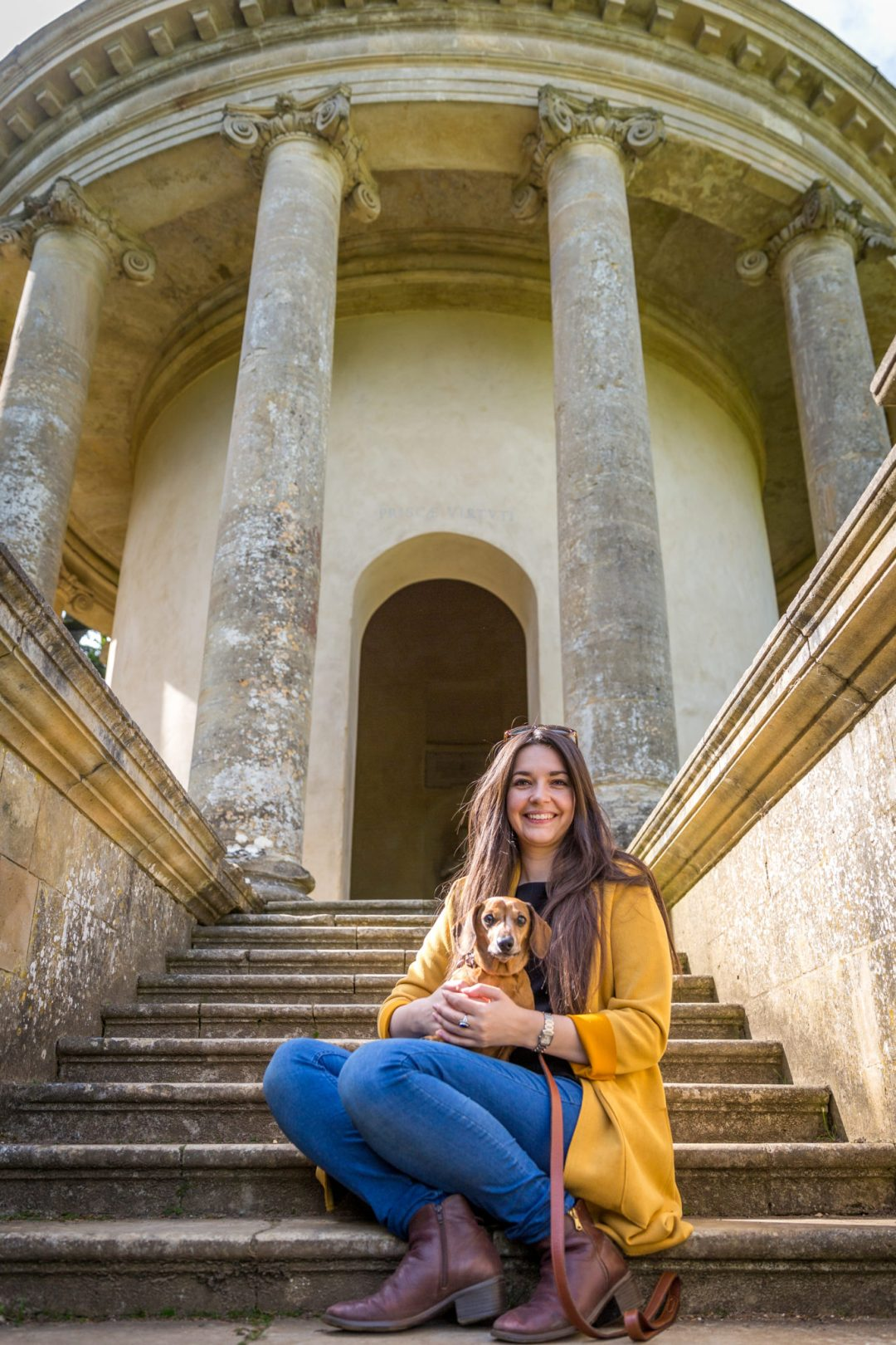 Click to discover why the National Trust dog walks at Stowe make an incredible day out with your dog. Picture shows Ted the dachshund & Sarah Baxter from Twilight Bark UK at the Ancient Temple of Virtue.