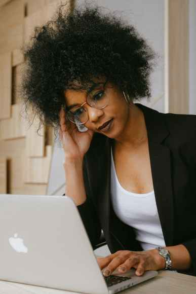 Black woman in black blazer wearing eyeglasses. She is stressed with a macbook in front of her