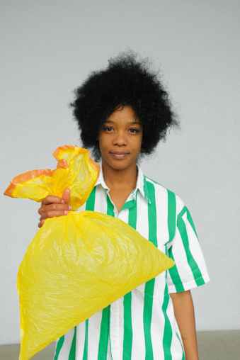 Black woman using her independence and holding yellow plastic bag