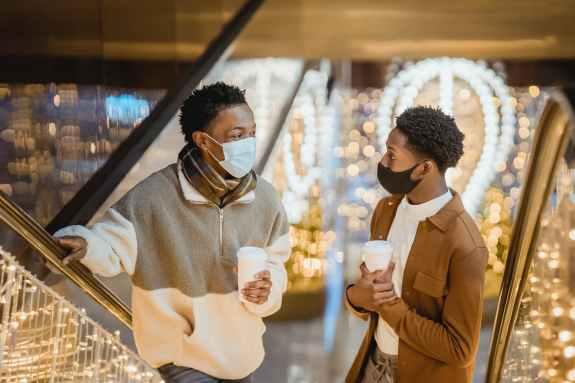 black friends with takeaway coffee talking between railings