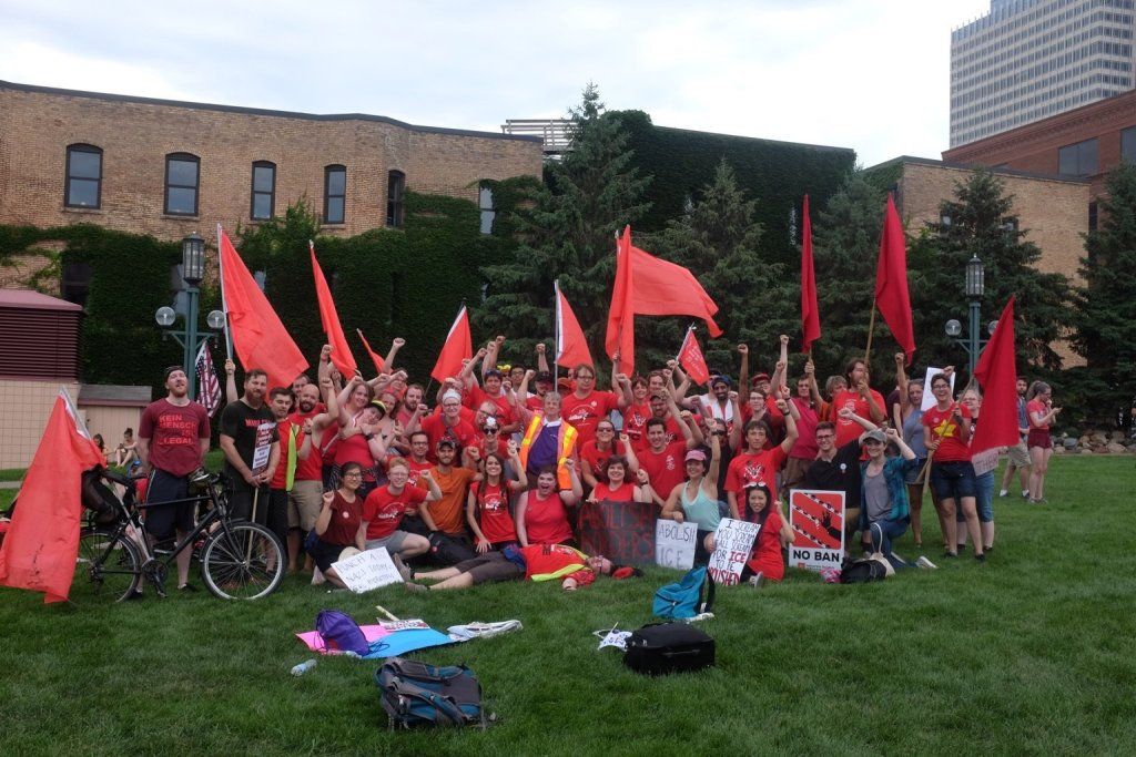 A large group of people mostly wearing red shirts, carrying red flags, posing for a picture on grass.