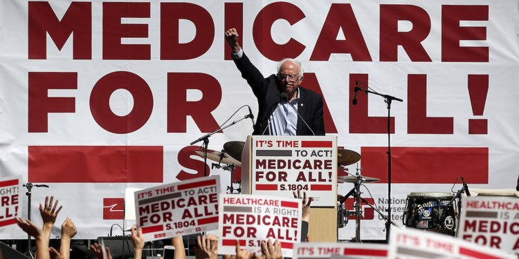 "Bernie Sanders delivering a speech, surrounded by ""Medicare for All"" signs."
